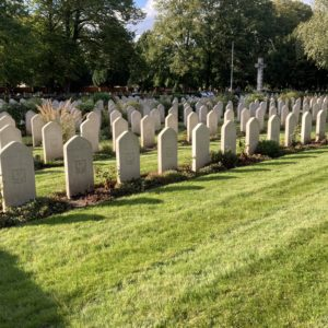 Rows of white headstones set into bright green grass